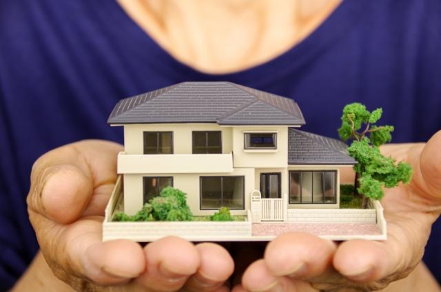 住宅の模型を持つ女性、相続